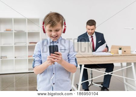 Business Attire Entrepreneur At Office With Boy Listening Music In Foreground