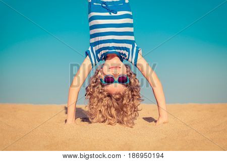 Funny Child Standing Upside Down On Sandy Beach