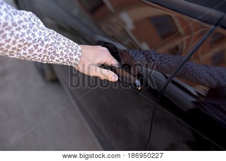 A hand holding a car's remote control pointing to the door. A man opens a machine
