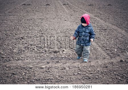 The Child Goes On A Field For Crops
