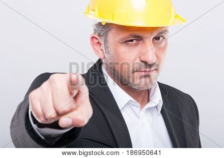 Close-up Of Foreman Wearing Hardhat Pointing Camera