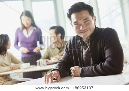 Smiling Asian man sitting in cafe