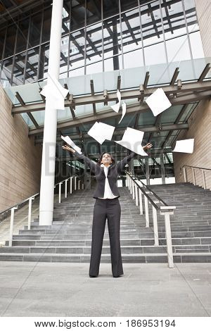 Indian businesswoman throwing papers into the air