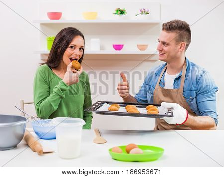 Young couple making cookies in their kitchen.