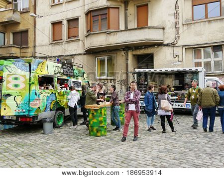 CLUJ-NAPOCA ROMANIA - MAY 7 2017: People have a snack at tables on the street. Food trucks sell tasty fast food.
