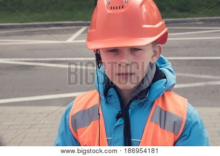 10 years old caucasian boy in safety helmet and reflective vest. Young engineer concept.