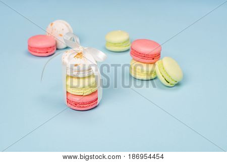 Colorful Macarons Tying With White Ribbon For Gift On Blue Surface. Still Life Of Fresh Macarons Con
