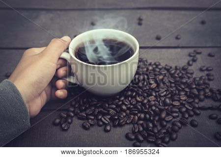 A woman's hand holds a coffee glass on a wooden table. With coffee beans