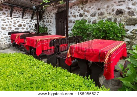 Bulgarian traditional restaurant with tables covered with red bulgarian tablecloth