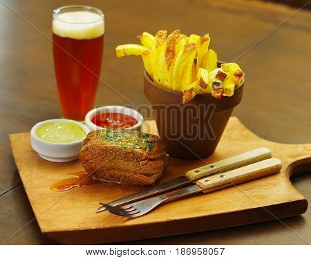 Close up of a well-done grilled marinated beef flank steak with ketchup, mustard and french fries with a glass of beer and a kitchen untensils on wooden board.