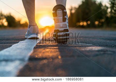 Runner feet running on road closeup on shoe. man fitness sunet jog workout welness concept on sunrise.