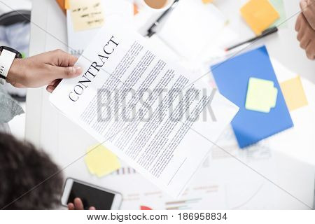 Overhead View Of Businessman Holding Contract Above Table With Papers