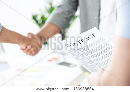 Close-up Partial View Of Businessmen Shaking Hands While Colleague Holding Contract