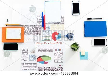 Top View Of Smartphones With Blank Screens, Papers And Office Supplies At Workplace