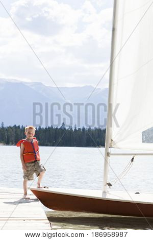 Boy in life jacket stepping onto a sailboat