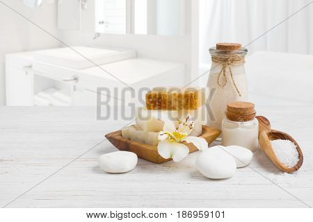 Spa products on wooden surface over blurred bathroom sink background