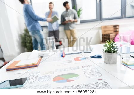 Close-up View Of Documents And Business Charts On Desk And Businessmen Standing Behind,  Business Te
