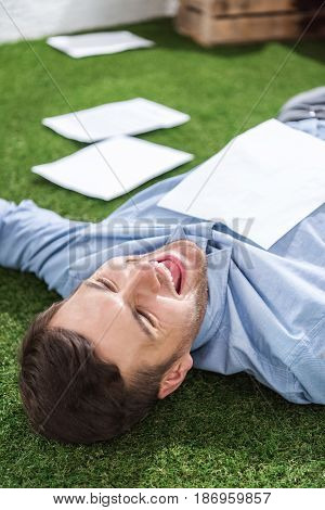 Side View Of Smiling Businessman Lying On Grass With Documents, Business Establishment  Concept