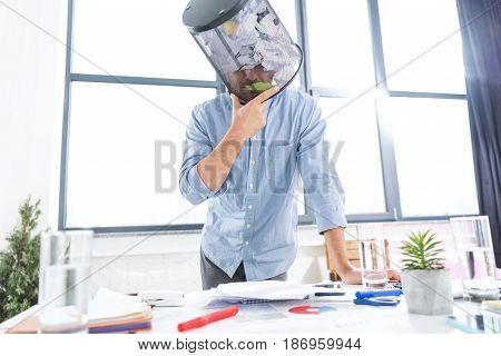 Portrait Of Pensive Businessman With Trash Bucket On Head In Office, Business Establishment