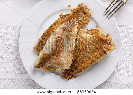 Fried rose fish fillet on a white plate. Sebastes norvegicus or ocean perch. Top view.