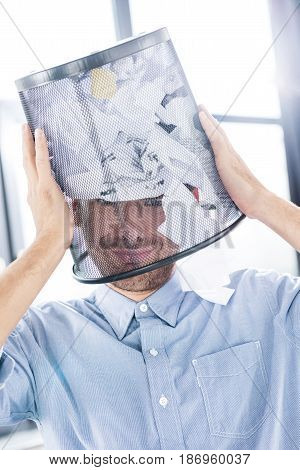 Portrait Of Smiling Businessman With Trash Bucket On Head In Office, Business Teamwork