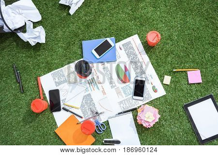Heap Of Business Objects And Office Supplies Laying On Green Grass Carpet At Office, Business Establ
