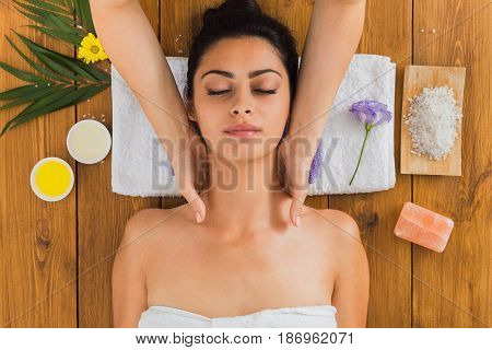 Neck massage in aroma spa wellness center, top view. Beautiful girl in cosmetology cabinet or beauty parlor.