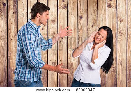 Digital composite of Angry man arguing with woman against wooden wall