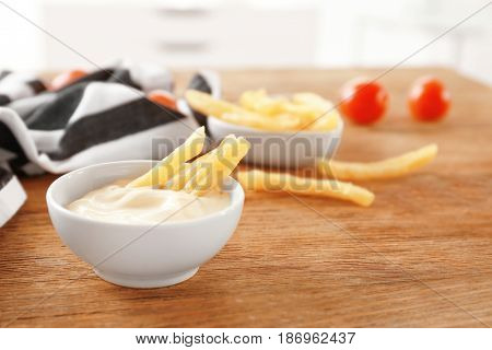 Bowl with tasty mayonnaise sauce and French fries on wooden table
