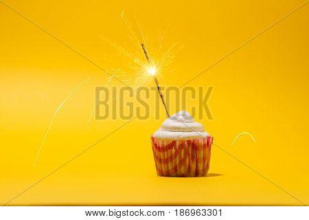 Birthday Cupcake With Firework On Yellow Background.