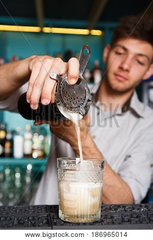 Professional bartender make cocktail, pouring coconut syrup into glass. Party time in night club. Service industry occupation