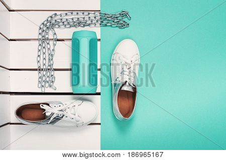 Flat Lay of Modern Womans Sport White Shoes. Overhead Top View Photography. Youth Lifestyle Concept. Square size. Turquoise background