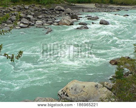 River in the Altai Mountains, Russia. Cloudy cold day. Rapids in water and rocks at the banks.