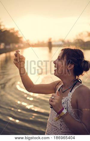 Caucasian woman taking photo sunset
