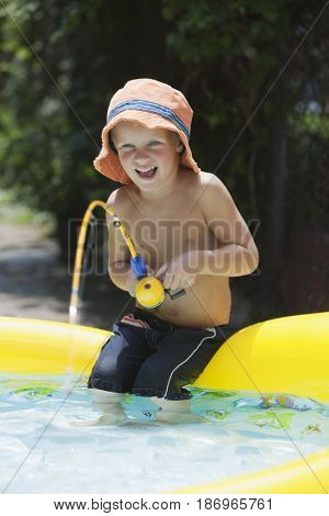 Caucasian boy fishing in kiddie pool