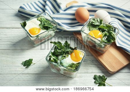 Portions of eggs Florentine on wooden background