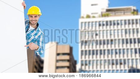 Digital composite of Portrait of smiling male architect pointing at blank billboard against buildings