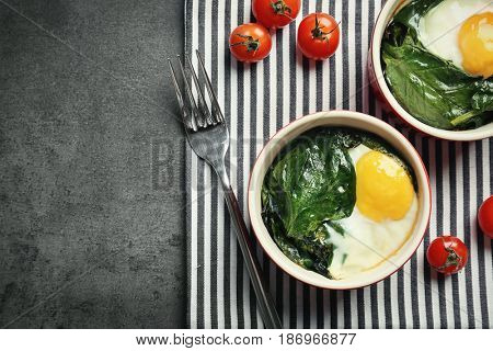 Portions of eggs Florentine with cherry tomatoes and striped napkin on grunge background