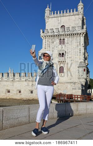 Young Caucasian woman taking a selfie photo at the Belem tower in Lisbon Portugal