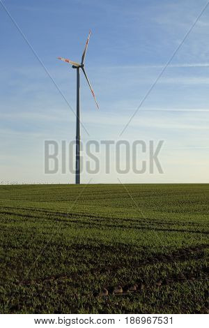 one wind wheel on a field at evening
