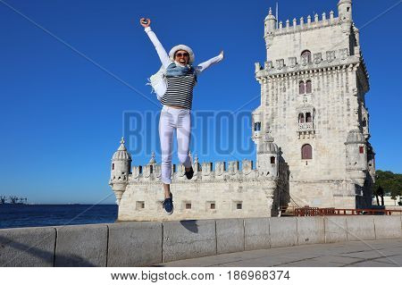 Young woman joyfully jumping in the background of Belem tower in Lisbon Portugal