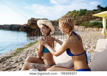 Young beautiful girls in swimwear smiling, applying suntan cream, sitting on chaises at seaside. Copy space.
