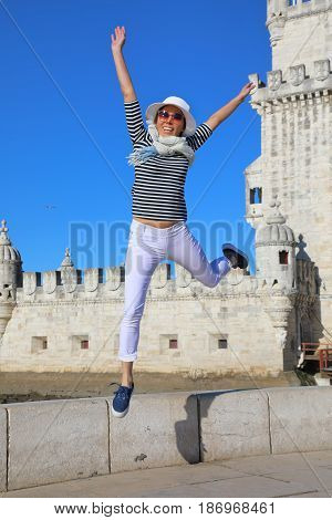 Young woman have fun jumping in the background of Belem tower in Lisbon Portugal
