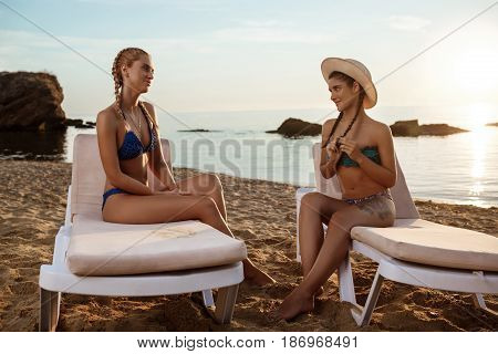 Young beautiful girls in swimwear smiling, sitting on chaises near sea. Copy space.