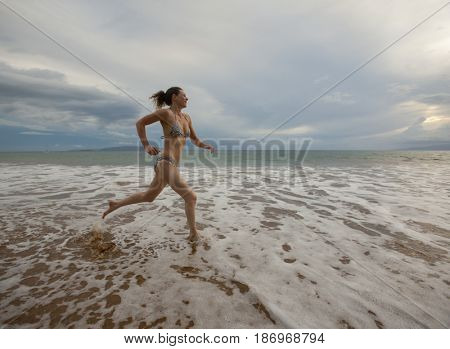 Caucasian woman in bikini running in ocean water