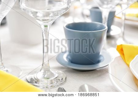 Wine glass and cup on table, closeup