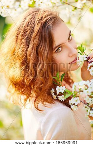 Young Beautiful Woman Enjoying Smell Of Blooming Tree On A Sunny Day (selective Dof)