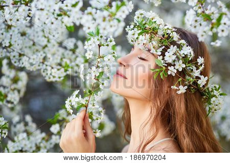 Young Beautiful Woman In Circlet Of Flowers Enjoying Smell Of Blooming Tree On A Sunny Day. Close Ey