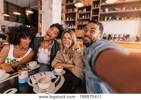 Young man taking selfie with friends making funny faces in a cafe. Crazy young people in a coffee shop making a self portrait.