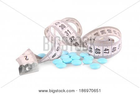 Diet concept. Measuring tape and pills on white background